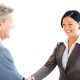 Portrait of successful business colleagues shaking their hands over white background