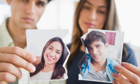 Couple holding torn photograph