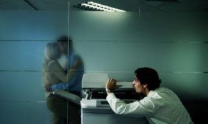 Office worker peeking from behind photocopier at couple kissing