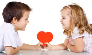 Two happy kids with valentines heart or birthday gift - isolated