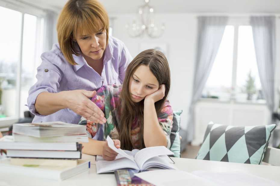 Mother assisting bored girl in studying at home