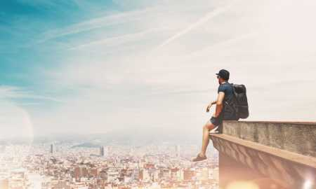Young man is sitting on a roof and looking at the city
