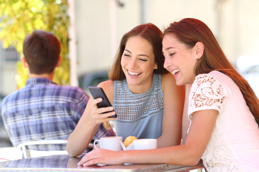 Two friends sharing a smart phone in a coffee shop