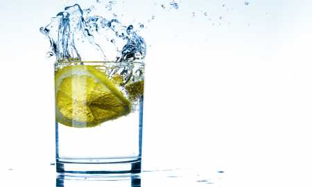 drink and refreshment concept - glass of sparkling water with lemon slices on reflective surface
