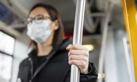 download-portrait-of-young-woman-using-public-transport-with-mask-for-free