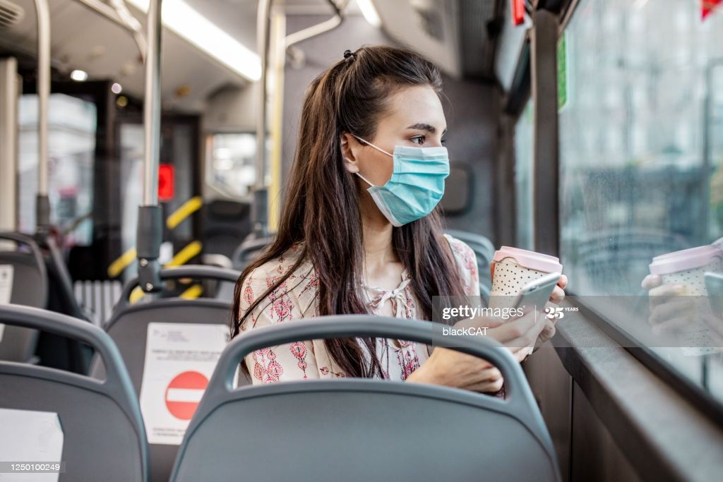 young-woman-wearing-a-protective-mask-while-sitting-in-a-bus-and___